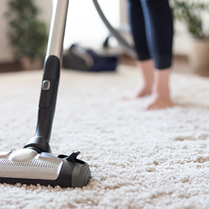 A woman hoovering a carpet