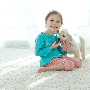 A young child and dog sitting on a carpet