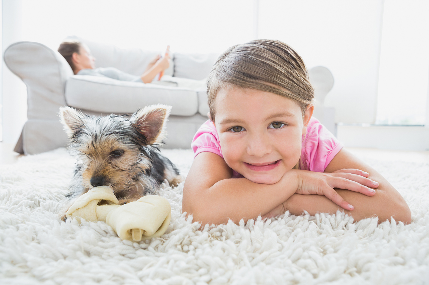 Yong child and pet dog laying on a carpet